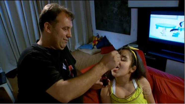 Fabio dá algumas gotas do óleo de cannabis para Clárian, durante uma reportagem do Fantástico