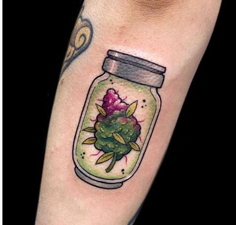 tatuagem de flor de maconha dentro de um pote
