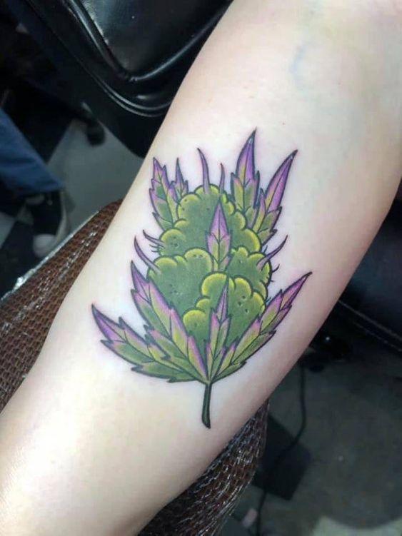 tatuagem de flor de maconha com tons roxos e verdes