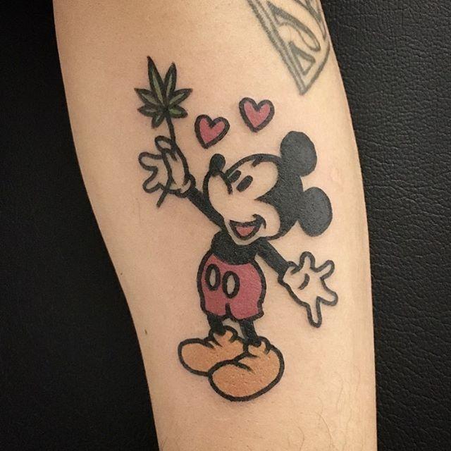 tatuagem do mickey segurando uma folha de maconha