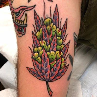 tatuagem da flor de maconha com tons roxos