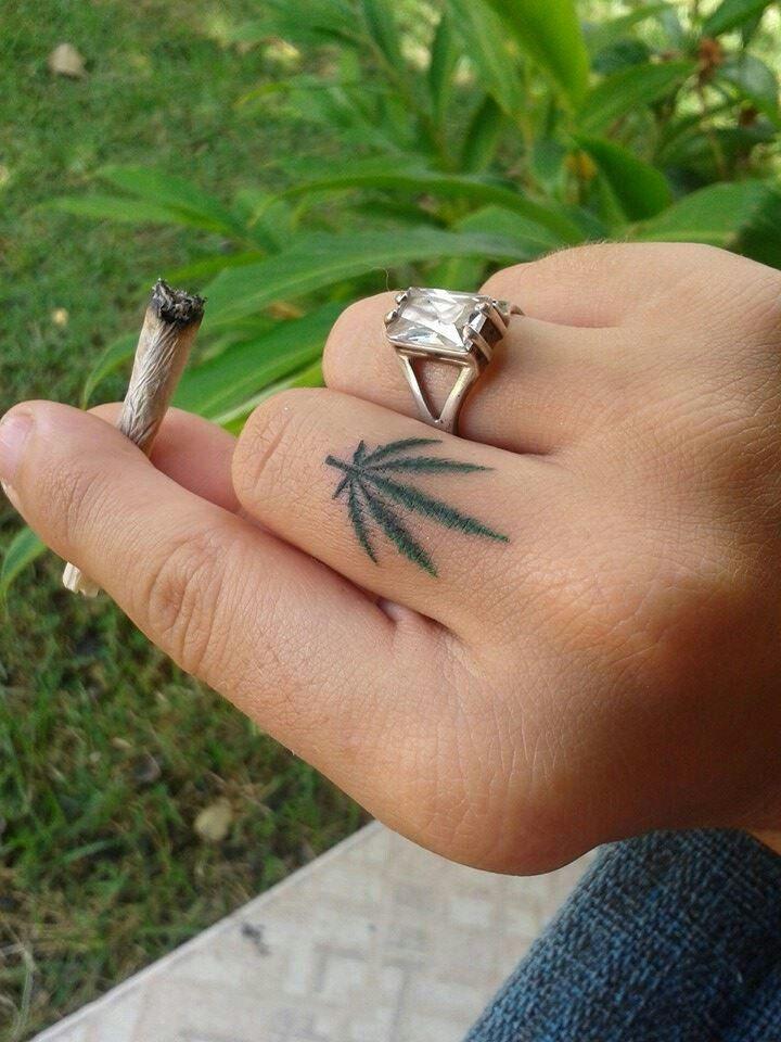 tatuagem de folha de maconha pequena no dedo
