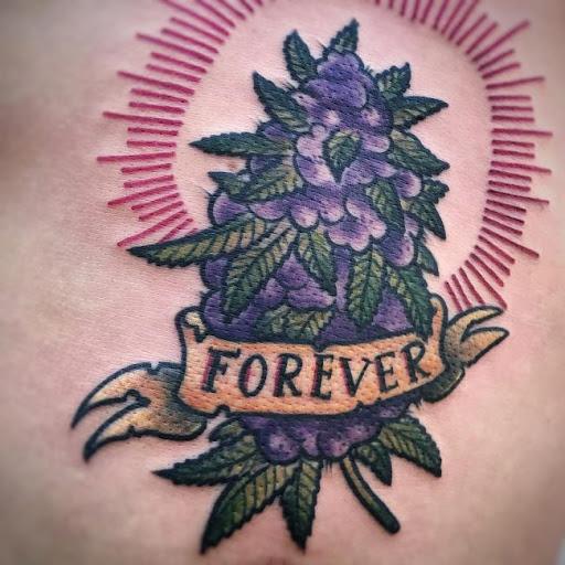 tatuagem da flor de maconha com tons roxos e uma faixa escrita forever